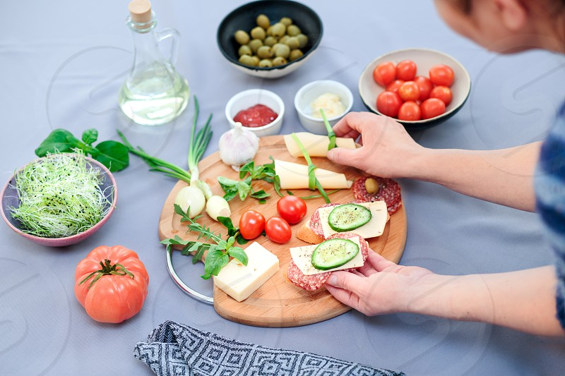Preparing healthy snacks with fresh cheese and vegetables photo