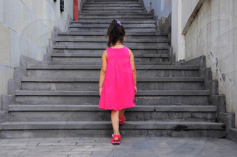 girl in pink tank mini dress walking on stairs photo