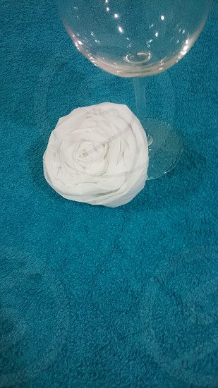 white vanity Fair napkin made into a flower next to a cup. photo