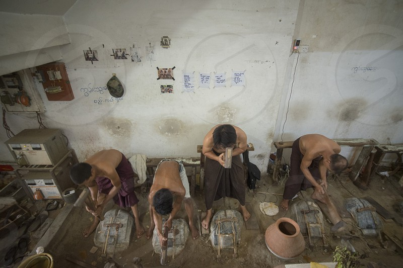 workers pound sheets of Gold leaf at a Gold pounder Factory the City of Mandalay in Myanmar in Southeastasia. photo