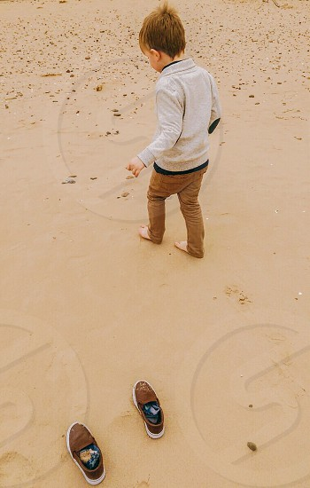 brown haired boy in gray jacket walking on brown sand during daytime photo