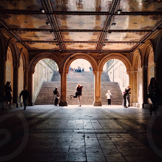 man carrying woman under the arc photo
