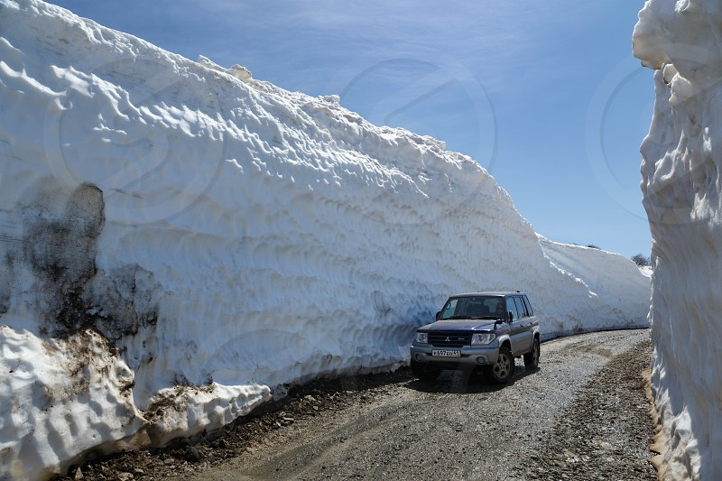 VILYUCHINSKY VOLCANO KAMCHATKA PENINSULA RUSSIA - JUNE 18 2017: Japanese off-road car Mitsubishi Pajero iO on mountain road in snow tunnel surrounded by high snowdrifts on Vilyuchinsky Pass. photo