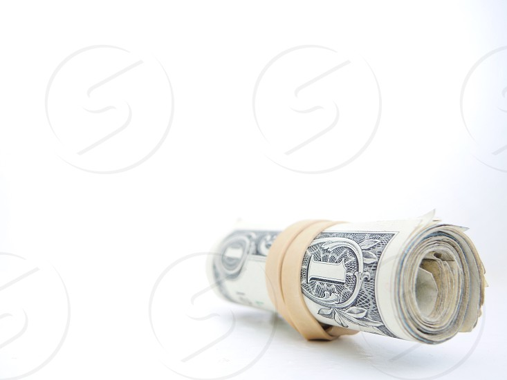 rolled 1 u.s dollar bill tied with white rubber band photo