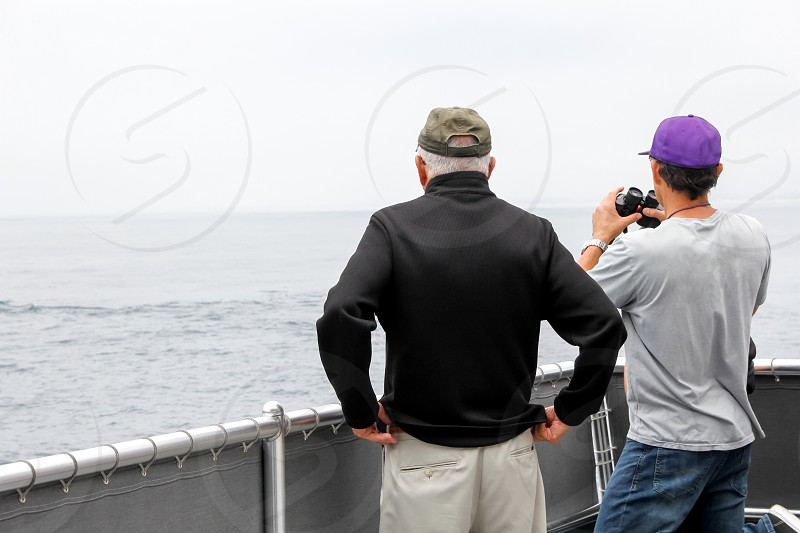 An old man and a middle aged man gaze out into the ocean. photo