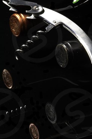 wine bottles with corkscrew on black background photo