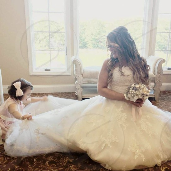 Wedding day bride flower girl bride and flower girl bridal suite getting ready little helper sweet sweet girl fluffing the dress little girls know it all adoring  photo