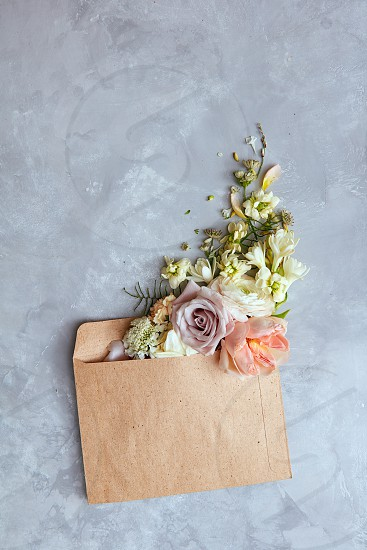 Flowers in envelope on the gray stone background. Mail for you. Spring background. Flat lay. photo