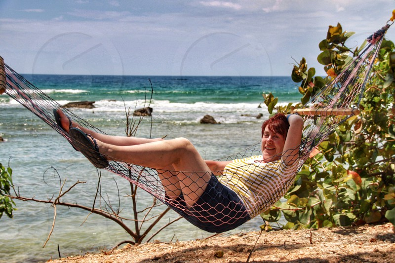 woman in yellow t shirt in a hammock photo