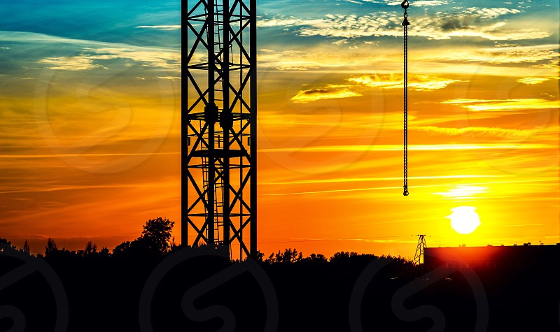 Sunset sunrise silhouette sky evening morning dramatic landscape cityscape skylight skyline sun cloud town travel beauty light night orange yellow crane city chain industrial outdoor nobody serenity colorful horizon structure scene scenic glow nature hdr  photo