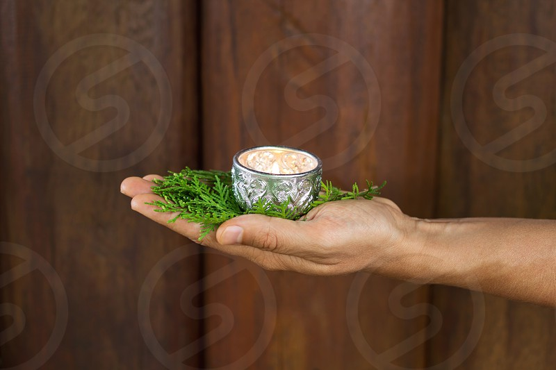 Christmas green juniper twigs and candle in hand photo