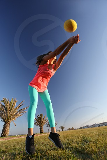 girl playing ball sky blue vibrant colours volley photo