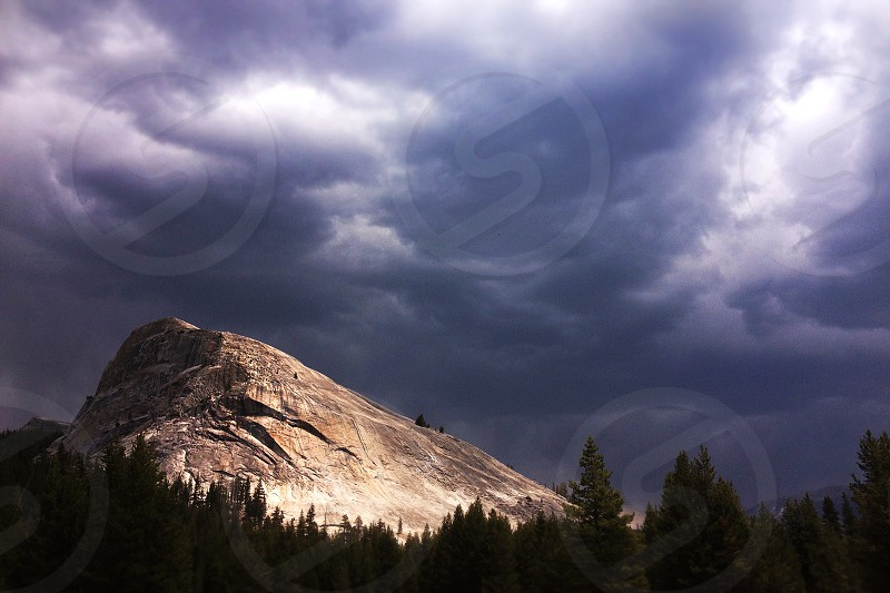grey clouds over the rocky mountain and trees photo