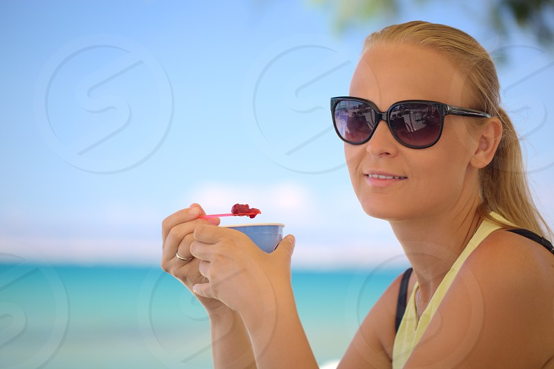 Young woman in sunglasses eating fruit ice-cream on the beach on a hot summer day. Bright blue sea and sky in background photo