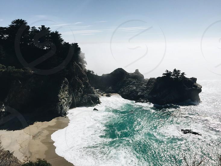 black rock mountain and green sea photo