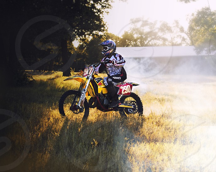 Dirt bike in scenic field of grass at sunset shows active lifestyle.  Sport shown in cloud of smoke behind the bike. photo