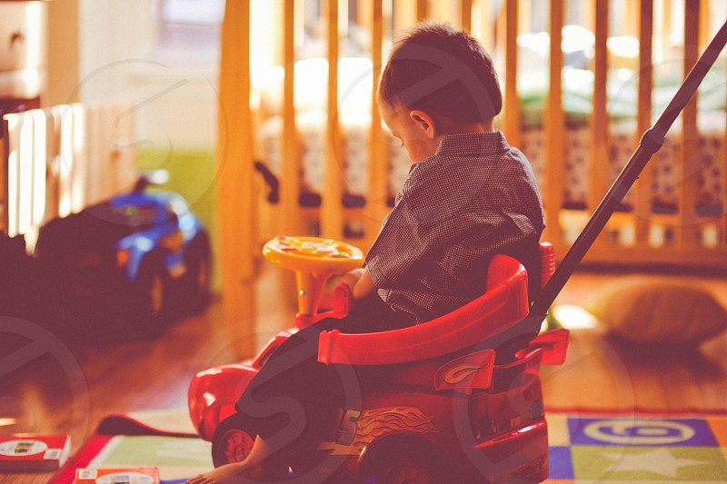 child on a red and yellow ride on vehicle photo