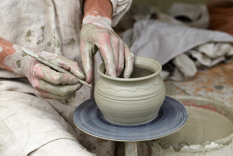 Potter's hands making a pot in a traditional style. photo