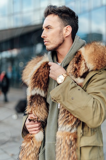 Fashionable man walk outdoors wear  fur jacket with street background - Image photo