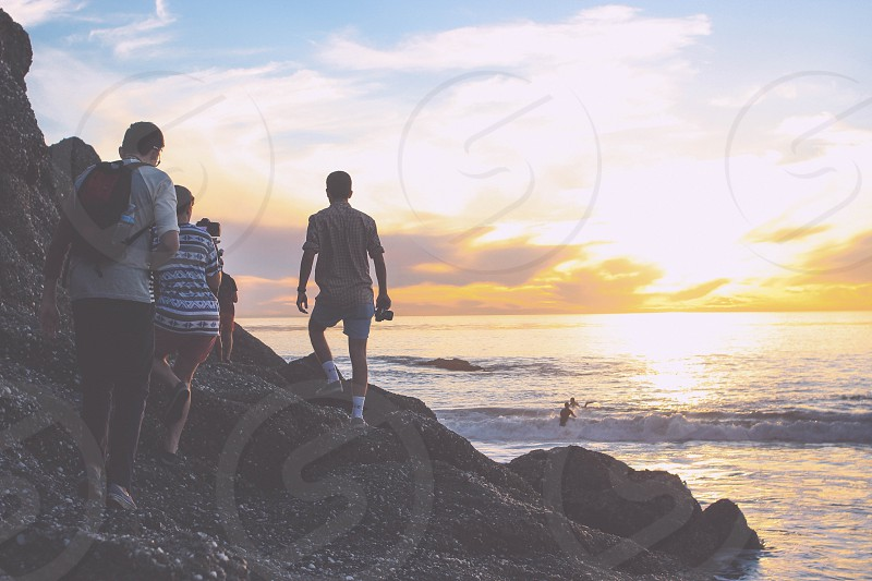people walking and standing near the sea photo