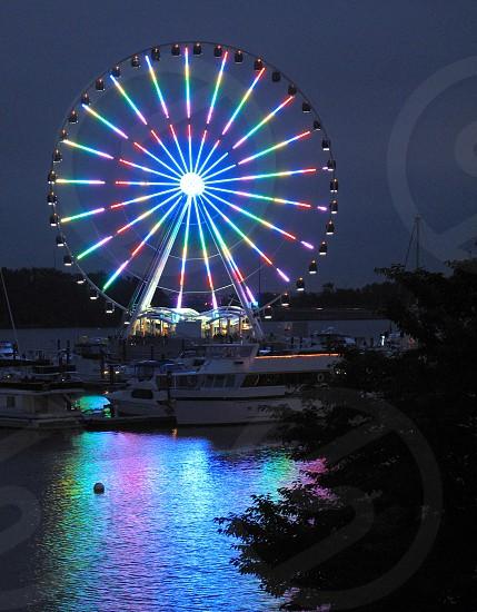ferris wheel amusement ride reflection boats yacht tree water night dusk Potomac River National Harbor Washington D.C. photo