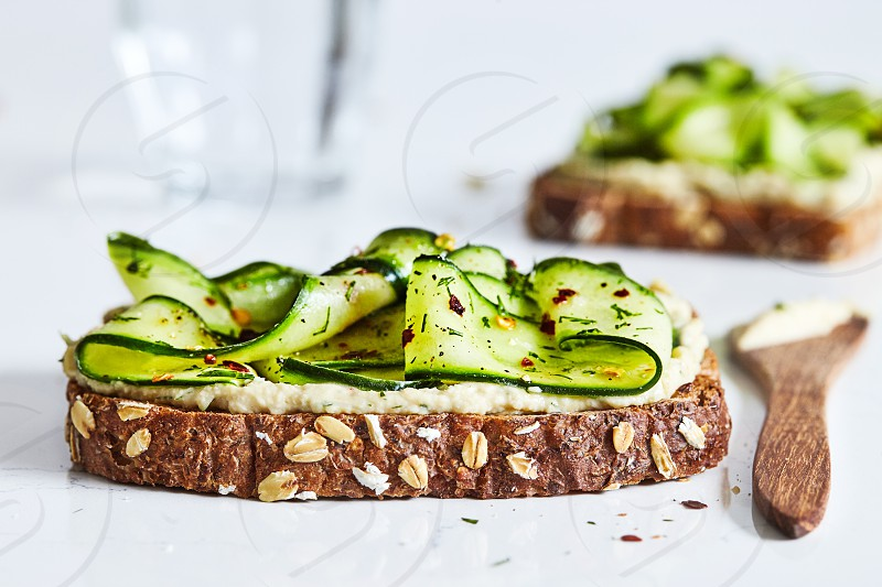 Whole grain toast with shaved cucumber hummus and dill. photo
