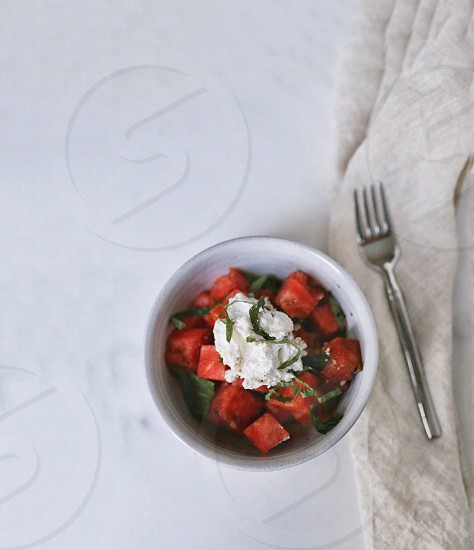 slice of watermelon on white  ceramic bowl filled with whip cream near stainless steel fork on white wooden surface photo