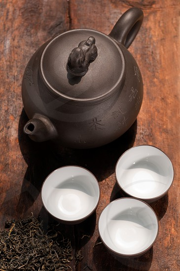 chinese green tea traditional  pot and cups over old wood board  photo