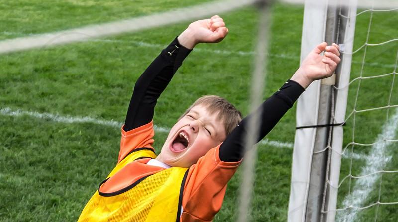 child standing near soccer goal photo