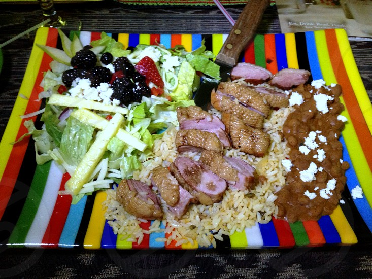 Duck on bed of rice with beans local cheese and locally sourced salad on striped plate photo