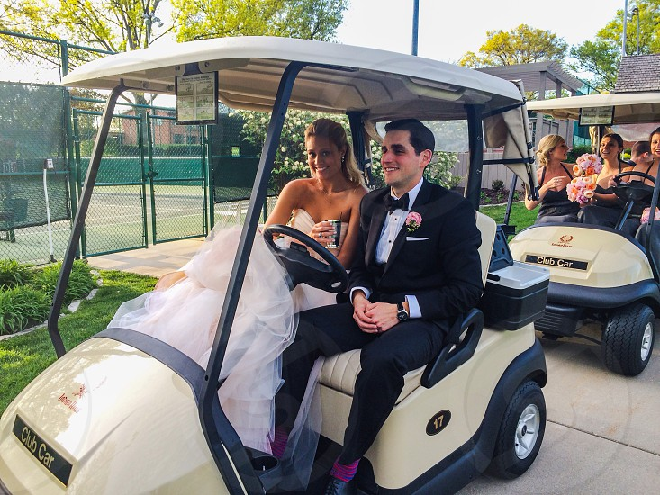 bride and groom in golf cart smiling photo