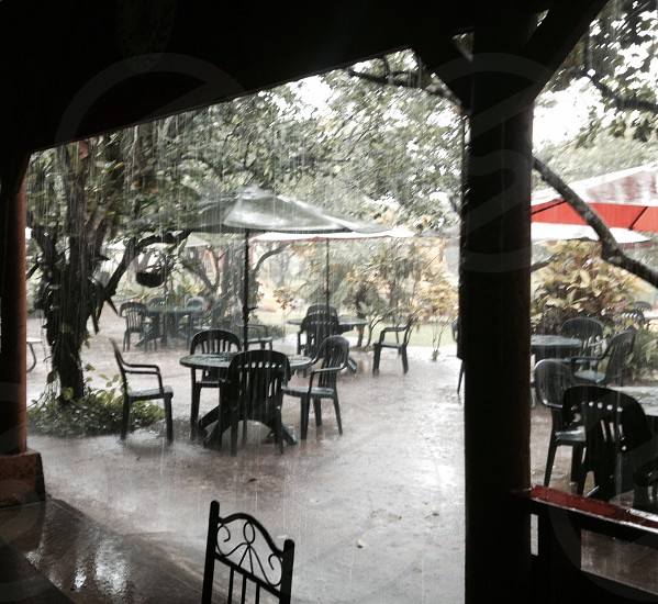 pouring rain on umbrella covered patio tables photo