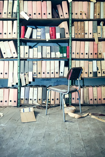 Library books bookshelf chair file read trim wood floor folders is attached sorted look up photo