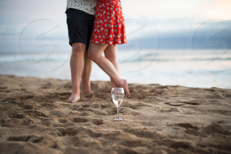 newly engaged couple enjoy the beach and a glass of wine together photo