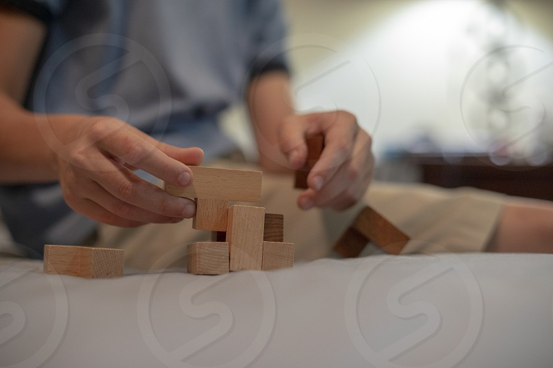 Child assembles wooden puzzle block photo