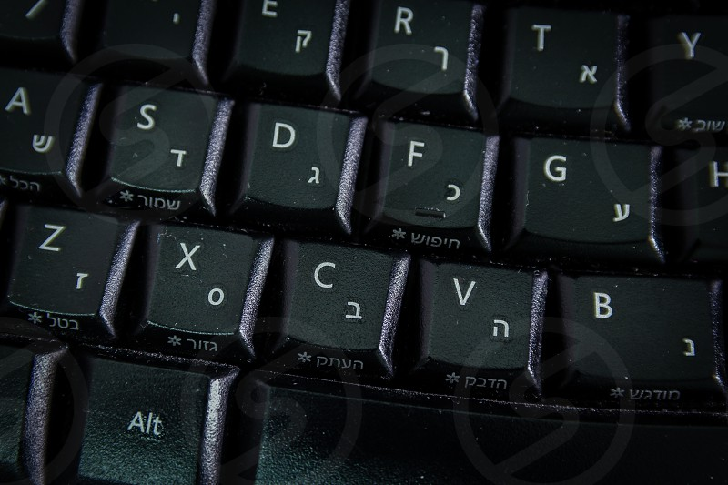 Keyboard with letters in Hebrew and English - Wireless keyboard - Top View - Close up - Dark atmosphere photo