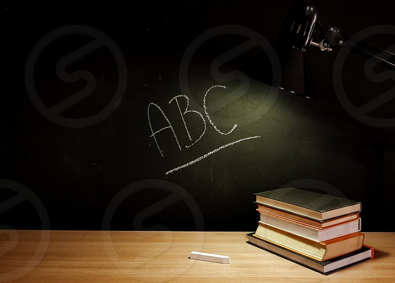 Back to school setting with a desk and black background. Books on a desk. Chalk written text on a blackboard. photo