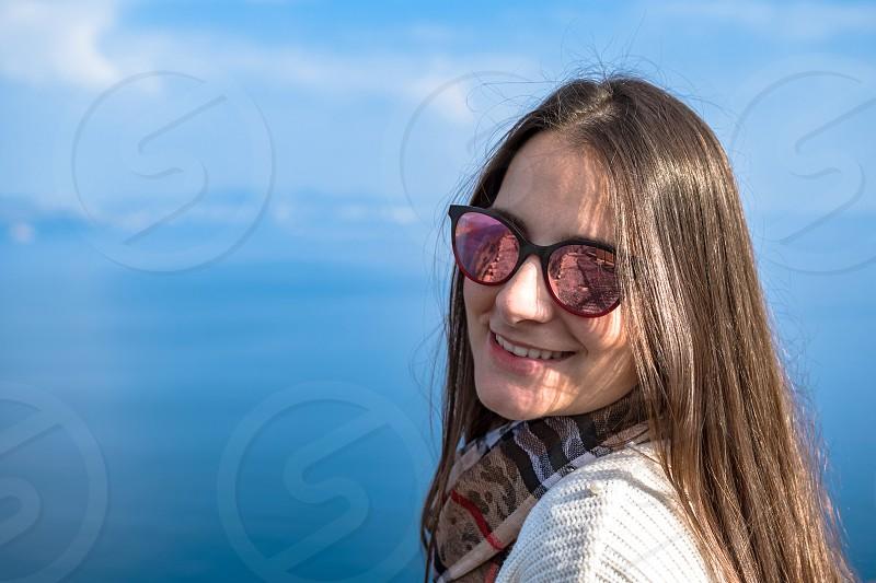 Cute girl wearing sunglasses on rock against foggy seascape photo