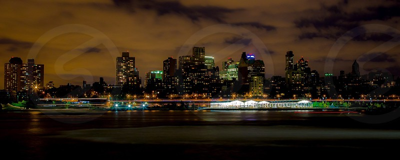 panorama photography of lighted high rise buildings under white cumulus clouds during night time photo