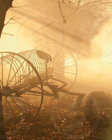 Light beams filtering through smoke around antique farm rake. photo