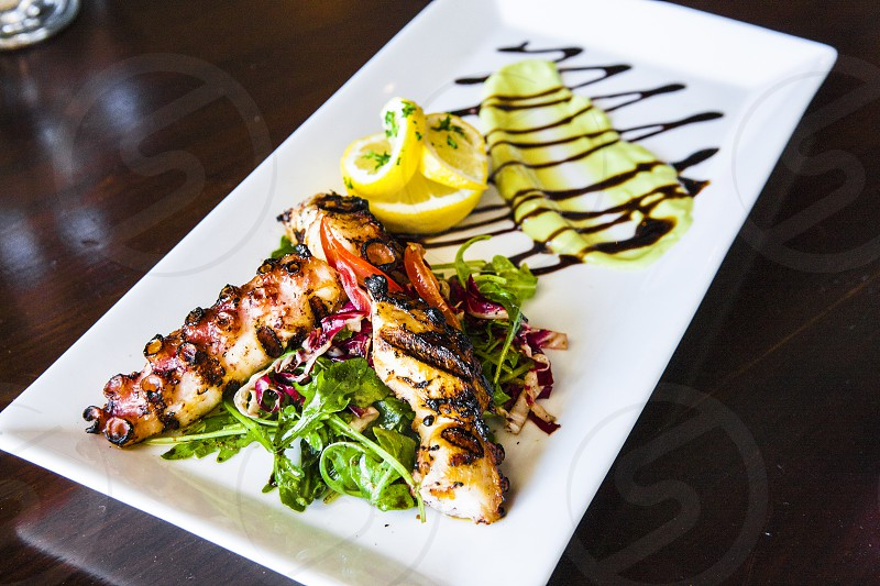 grilled squid tentacles with green leaf sliced lemon and chocolate syrup on white ceramic rectangular plate photo