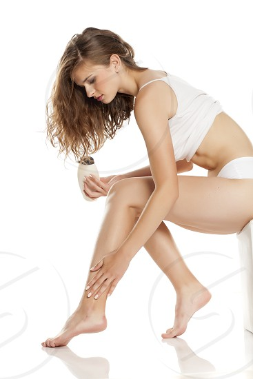 Young woman applying cream on her legs on white background photo