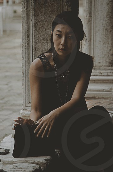 woman in black sleeveless dress holding her black purse sitting by the concrete post photo