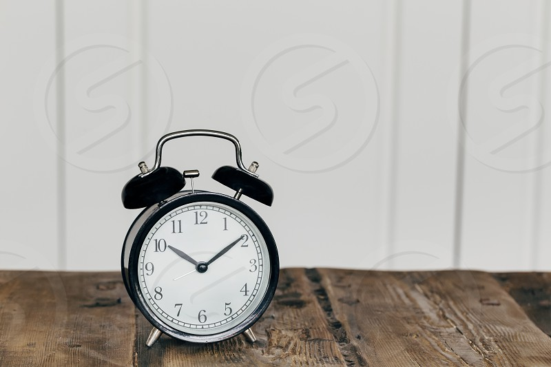 time black clock alarm clock wooden table copy space  photo