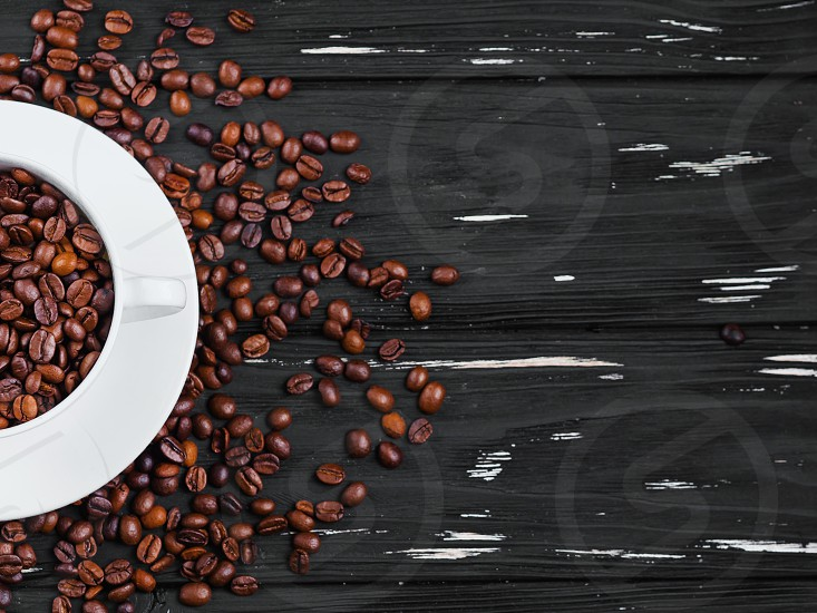 Porcelain white coffee cup and beans on black shabby wooden background. Top view. photo