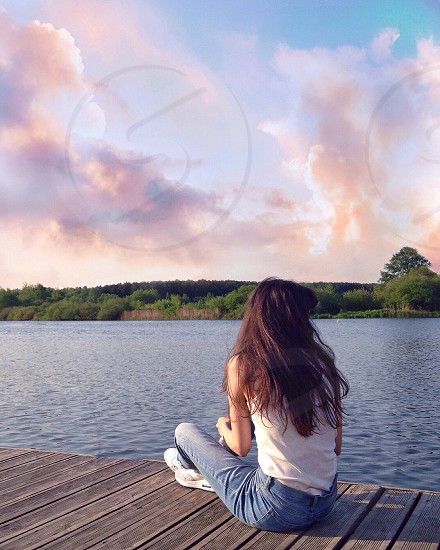 woman with brown long hair in white tank top and blue denim jeans sitting on brown wooden dock looking at body of water during daytime photo