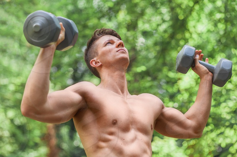 Muscular young man lifting weights outside in the park photo