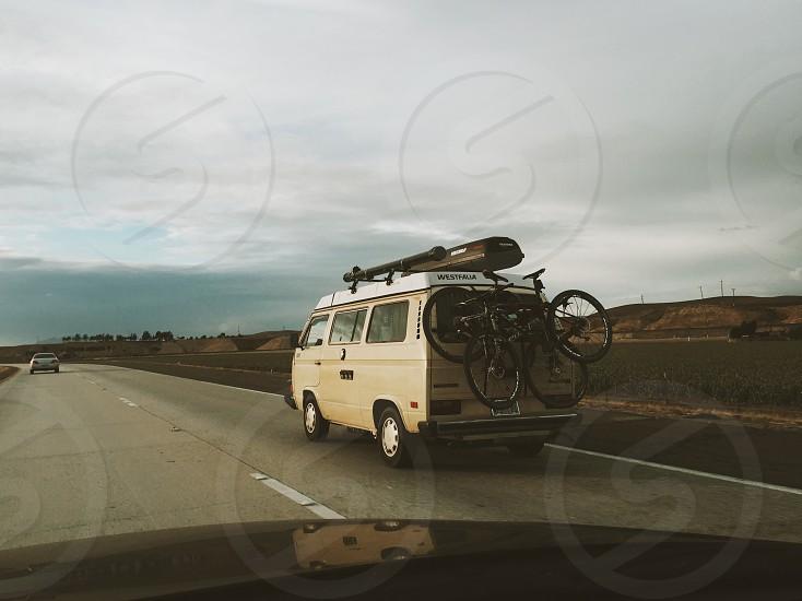 white van carrying 2 mountain bike under grey sky during daytime photo