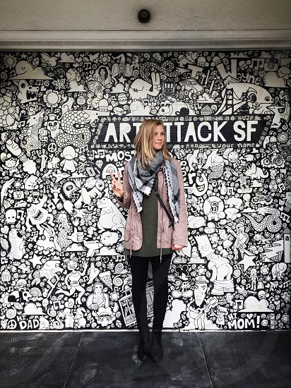 blond woman in grey scarf mauve coat and black leggings standing against black and white graphic wall with art attack sf sign photo