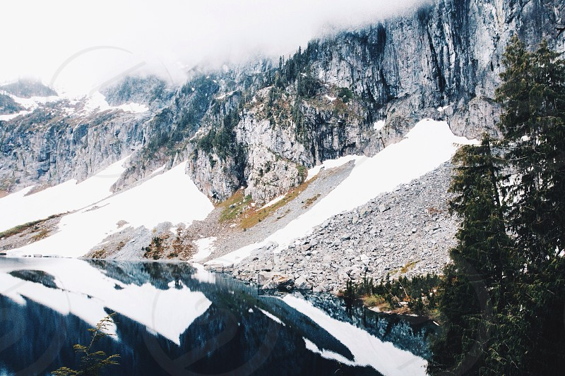 mountain slopes with snow beside a lake photo